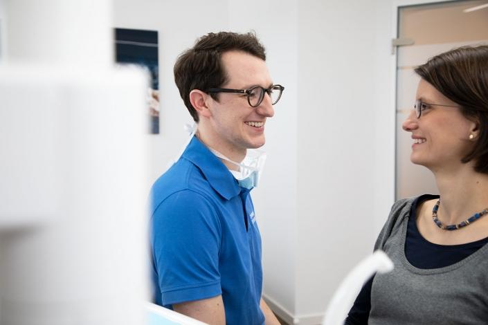 Zahnarzt in Augsburg Eschlberger lacht mit einer Patientin